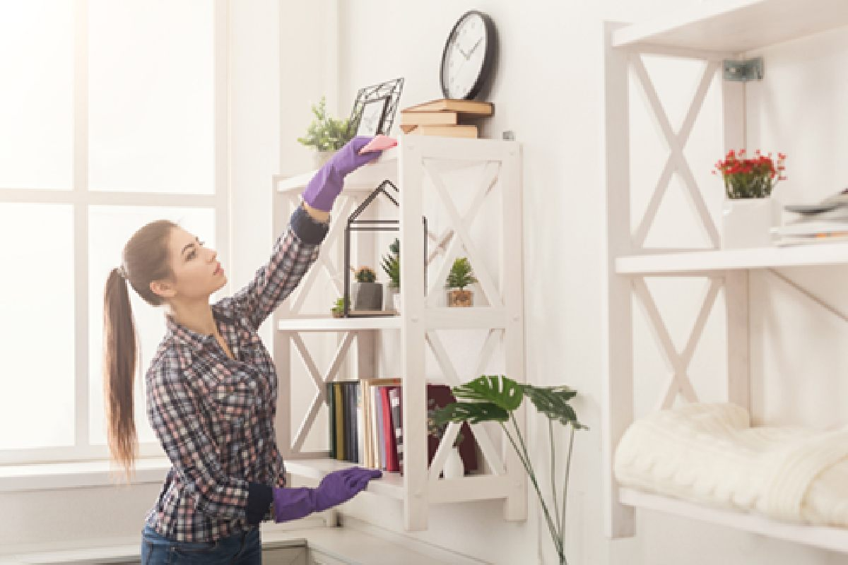 A woman cleans her living room